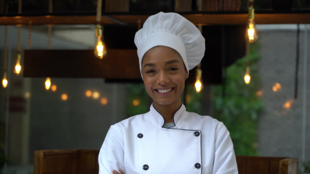 Beautiful black female chef smiling at camera with arms crossed Beautiful black female chef smiling at camera with arms crossed in a restaurant commercial kitchen stock videos & royalty-free footage