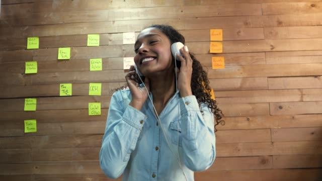 vacker svart kvinna avkopplande kvinnliga på kontoret att sätta hennes hörlurar på ser väldigt glad - latino music bildbanksvideor och videomaterial från bakom kulisserna