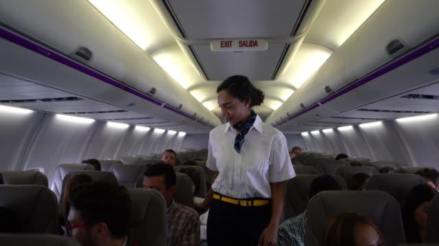 아름 다운 검은 승무원 모두 걸릴 하기 전에 그들의 안전 벨트를 착용 하는 운영 체제 확인 - airplane seat 스톡 비디오 및 b-롤 화면