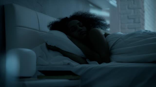 vídeos y material grabado en eventos de stock de hermosa chica negra durmiendo en la cama por la noche - dormir