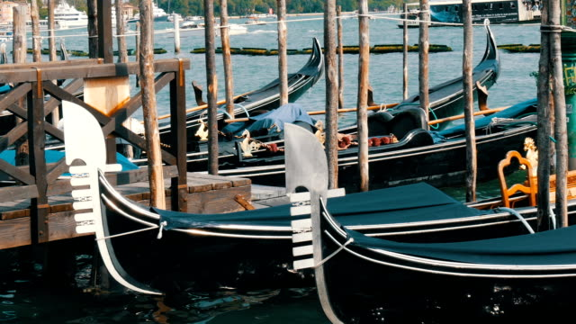 Beautiful black gondolas stand and rock on the waves of Grand Canal in Venice