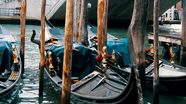 Beautiful black gondolas with gilded figures stand parked under a world famous Rialto Bridge
