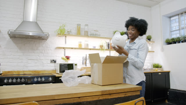 Beautiful black woman at home receiving a parcel and unpacking a white piggy bank