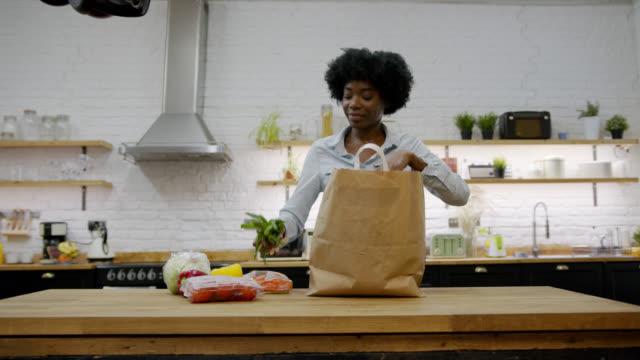自宅で彼女の食料品を開梱し、非常に幸せそうに見える野菜の匂いを嗅ぐ美しい黒人女性 - 荷物をとく点の映像素材/bロール