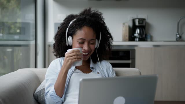 vídeos de stock, filmes e b-roll de linda mulher negra em casa assistindo um filme no laptop usando fones de ouvido e desfrutando de um chocolate quente - café bebida