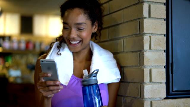 vacker svart kvinna chattar på hennes smartphone efter en träning på gymmet - black woman towel workout bildbanksvideor och videomaterial från bakom kulisserna