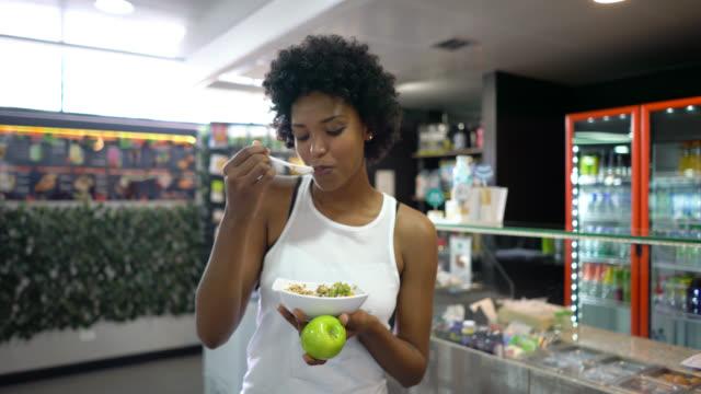 beautiful black woman enjoying a cereal bowl with fruits after working out at the gym - chudy filmów i materiałów b-roll