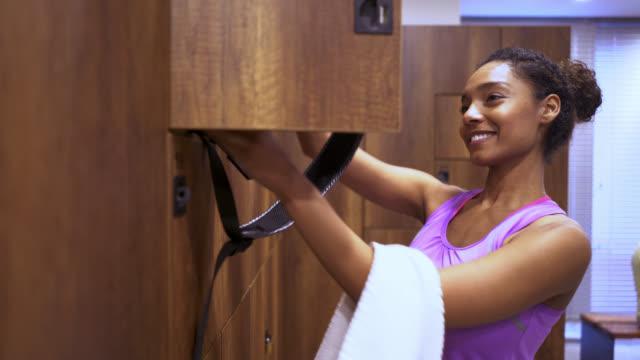 vacker svart kvinna kommer in i omklädningsrummet på gymmet - black woman towel workout bildbanksvideor och videomaterial från bakom kulisserna