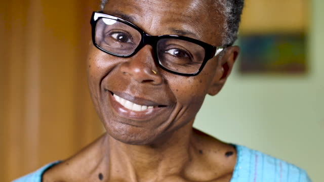 Beautiful black woman in her 60s smiling and looking at the camera