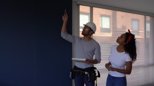 beautiful black woman owner of apartment talking to building contractor while he points at different things holding a clipboard - imprenditore edile video stock e b–roll