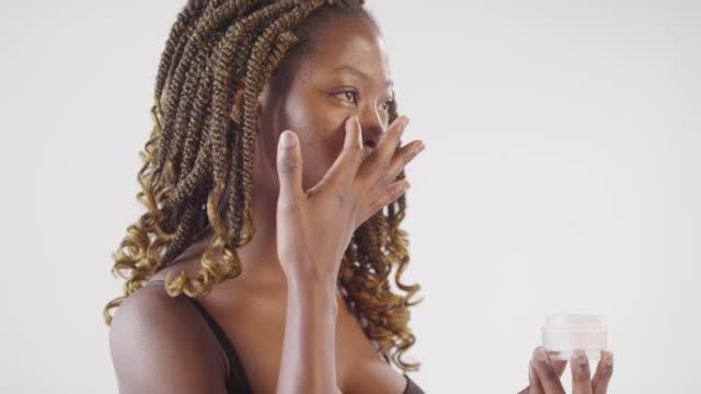 Beautiful Black Woman Putting Cream on Face