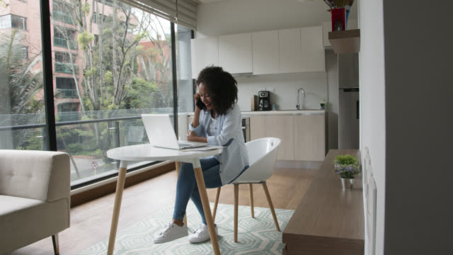 Beautiful black woman receiving a phone call while working on laptop at home looking very happy