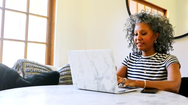 beautiful black woman using laptop at home - siwe włosy filmów i materiałów b-roll