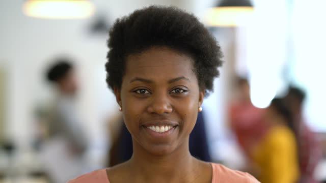 stockvideo's en b-roll-footage met mooie zwarte jonge vrouw op kantoor kijken naar de camera glimlachen - portrait background