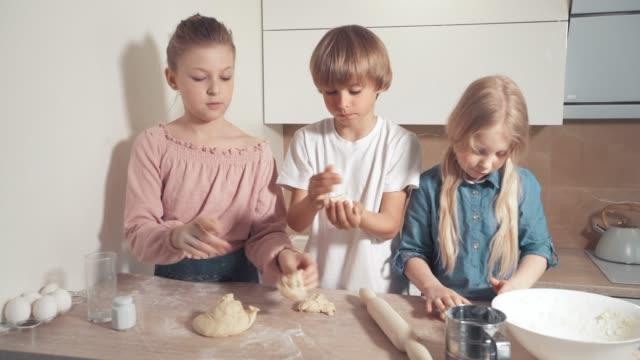 Beautiful blond children sculpt cookies from dough in a bright kitchen.