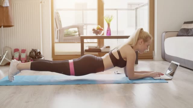 beautiful blond sporty woman doing her workout at home while watching online lessons - metodo pilates video stock e b–roll