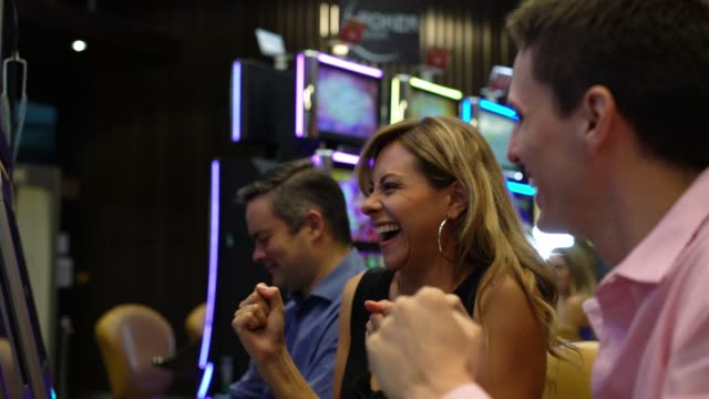 Beautiful blond woman celebrating a win on slot machines at the casino and man sitting next to her celebrating too