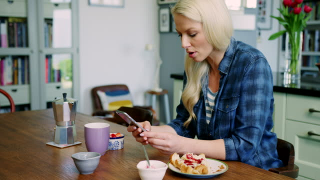 Beautiful Blond Woman Checking Smart Phone At Breakfast Table Tilt up shot of beautiful blond woman checking her smart phone at the kitchen table. Young lady is surfing the internet while having her breakfast. Female doing online browsing,  checking her social media feed and staying connected. There is a croissant,  coffee and berries on the table. Slow motion. Shot on RED Camera. mid adult women stock videos & royalty-free footage
