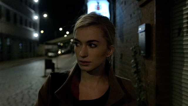 Beautiful blond woman in coat walking alone outdoors at night. video