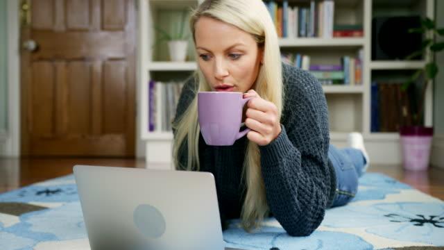 güzel sarışın kadın çay içme dizüstü kullanarak halıya yalan - coğrafi konum stok videoları ve detay görüntü çekimi