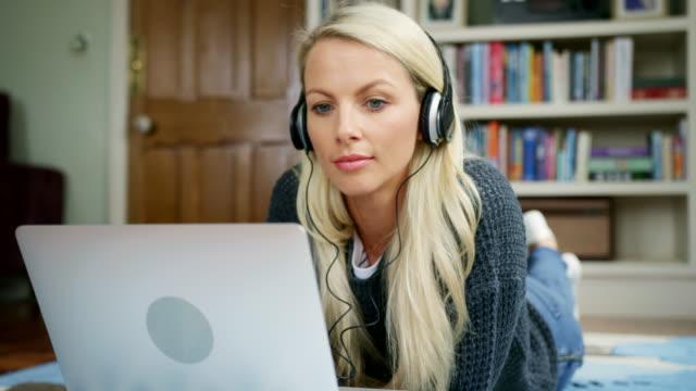 vídeos y material grabado en eventos de stock de hermosa mujer rubia en la alfombra usando laptop - descargar internet