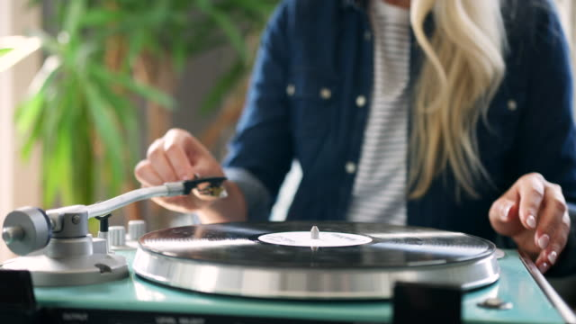 vídeos de stock e filmes b-roll de beautiful blond woman putting vinyl on turntable - hygge