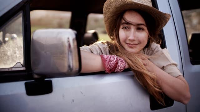 vidéos et rushes de belle femme blonde assis dans une camionnette et rêverie - culture américaine