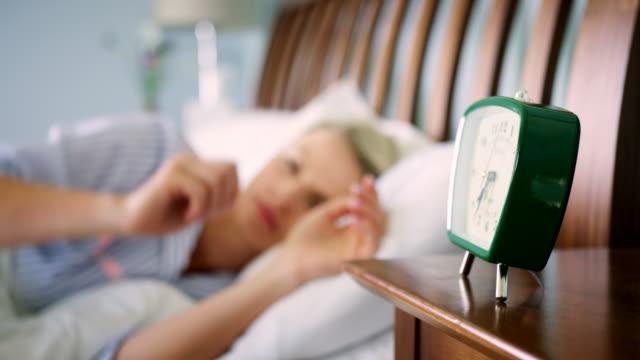 beautiful blond woman switching off her alarm clock - sonnecchiare video stock e b–roll