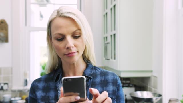 schöne blonde frau sms auf smart phone in küche - koffeinmolekül stock-videos und b-roll-filmmaterial