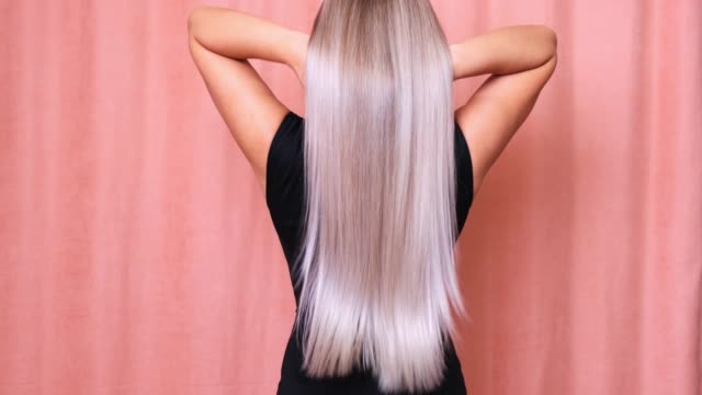 Beautiful blond woman throws her long wavy hair. Hair care concept