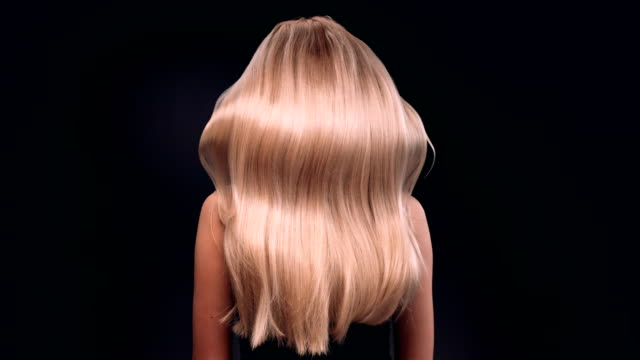 beautiful blond woman tossing her long, wavy hair - capelli biondi video stock e b–roll