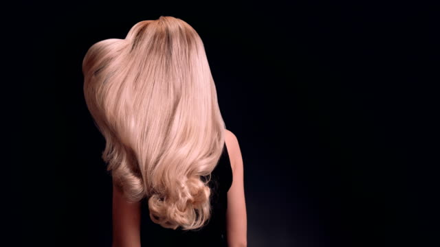 Beautiful blond woman tossing her long, wavy hair Studio shot of attractive dark blond woman tossing her healthy, long hair. Super slow motion. long hair stock videos & royalty-free footage