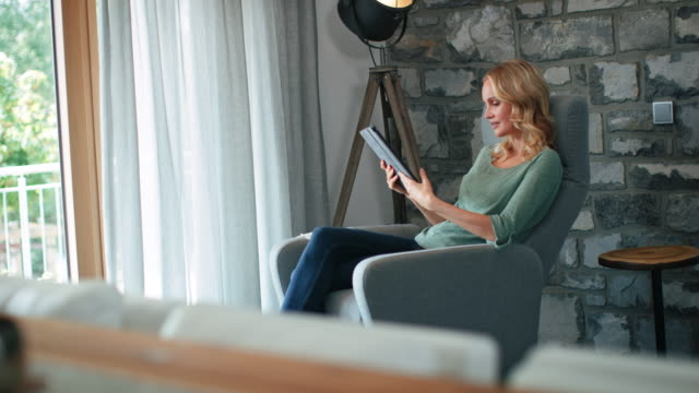 Beautiful blond woman using digital tablet at home Handheld shot of smiling beautiful female using digital tablet. Blond woman is sitting on chair with legs crossed. She is against wall. chair stock videos & royalty-free footage