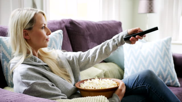 vídeos de stock e filmes b-roll de beautiful blond woman using tv remote control sitting on sofa - hygge