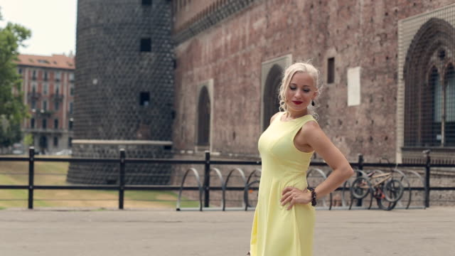Beautiful blond woman with bright red lips posing next to the old castle in Milan video