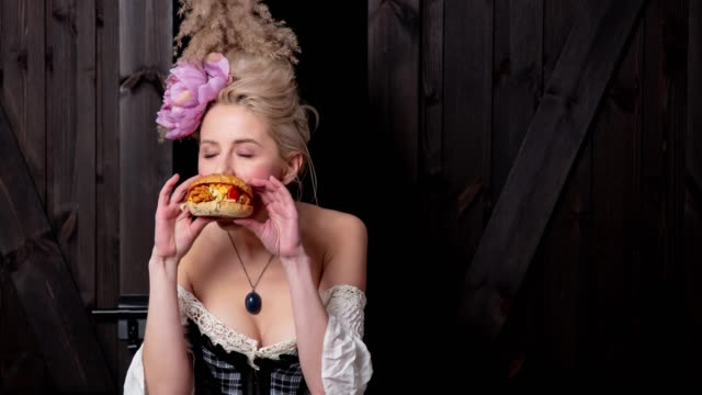 Beautiful blonde countess with burger Beautiful blonde countess with burger on wooden background renaissance architecture stock videos & royalty-free footage