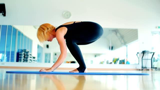 schöne blonde mädchen, die yoga in der turnhalle des sports - haarfarbe stock-videos und b-roll-filmmaterial
