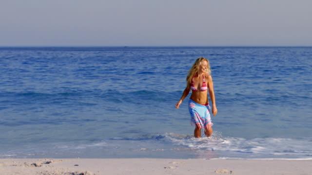 beautiful blonde having fun into the sea - sarong bildbanksvideor och videomaterial från bakom kulisserna
