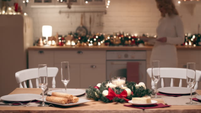 a beautiful blonde is preparing for the arrival of guests for christmas dinner. she sets a festive table in the kitchen in her house. - christmas table video stock e b–roll