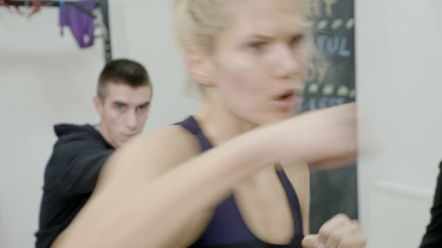 Beautiful blonde kickboxing female instructor with a fit body training at the gym using punching moves and men following her video