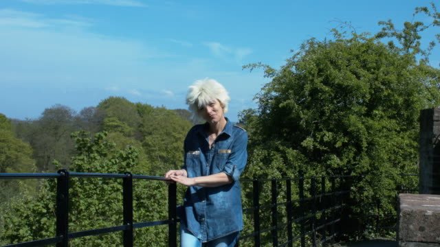 A Beautiful Blonde Lady Enjoying A Sunny Day At A Park Balcony video