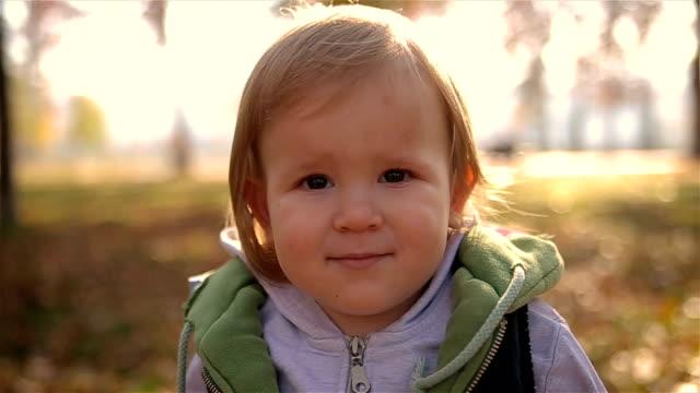 Güzel sarışın bir çocuk kameraya bakıyor video