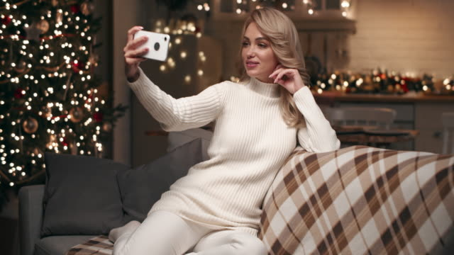 beautiful blonde makes a christmas selfie at home in the living room on the background of a christmas tree. - treedeo christmas stock videos & royalty-free footage