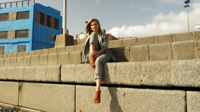 beautiful blonde model with high heels by the concrete stairs - blazer video stock e b–roll