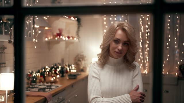 stockvideo's en b-roll-footage met een mooie blonde op kerstavond staat aan het raam tegen de achtergrond van de keuken versierd met kerstverlichting en kijkt naar de straat. - christmas cabin