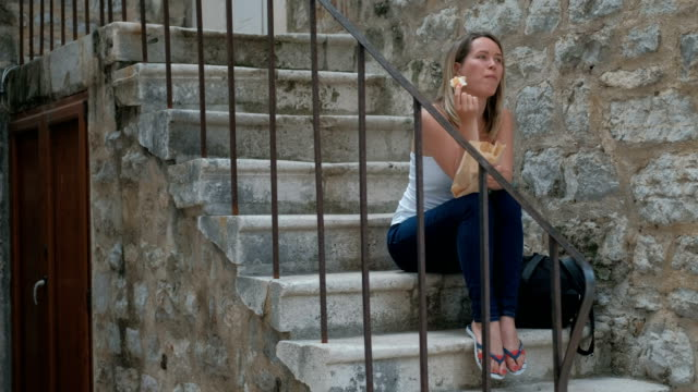 Beautiful blonde sitting on the stone steps and eat a meal video