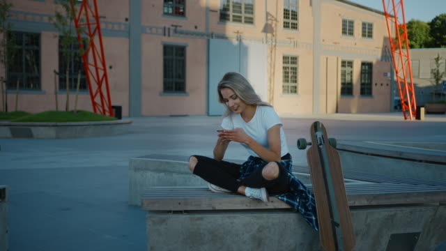 Beautiful Blonde Skater Girl Wearing Casual Clothes, Uses Smartphone, Sharing Stuff on Social Media, Taking Selfies, Messaging Friends and Having Fun while Sitting on a Bench in Fashionable Hipster
