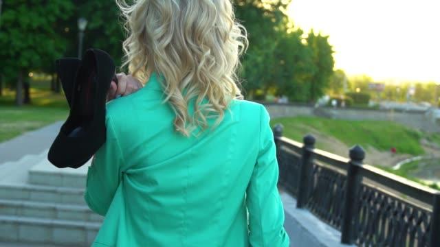 güzel sarışın gezinti boyunca yürüyor. nazik kız omzuna ayakkabı giyer, yorulur. poz. kafkas, avrupa görünümü. yavaş çekim. - i̇nsan sırtı stok videoları ve detay görüntü çekimi