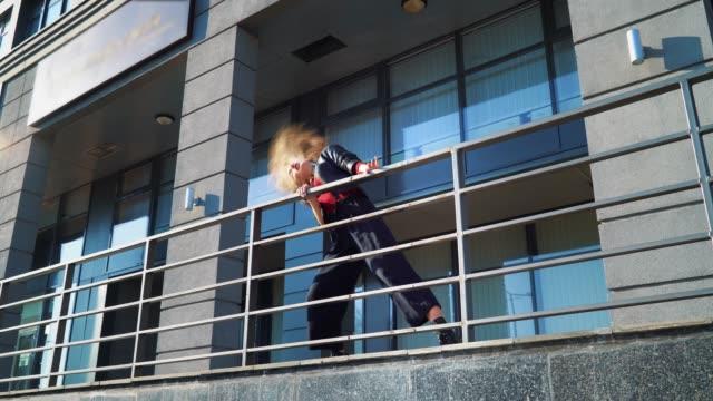 beautiful blonde woman dancing near metal railings on city street - top nero video stock e b–roll