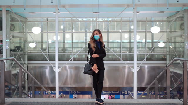 Beautiful blonde woman in black business suit wearing protective face mask in public places and keeping social distance, pretty female standing on background of modern office with transparent windows